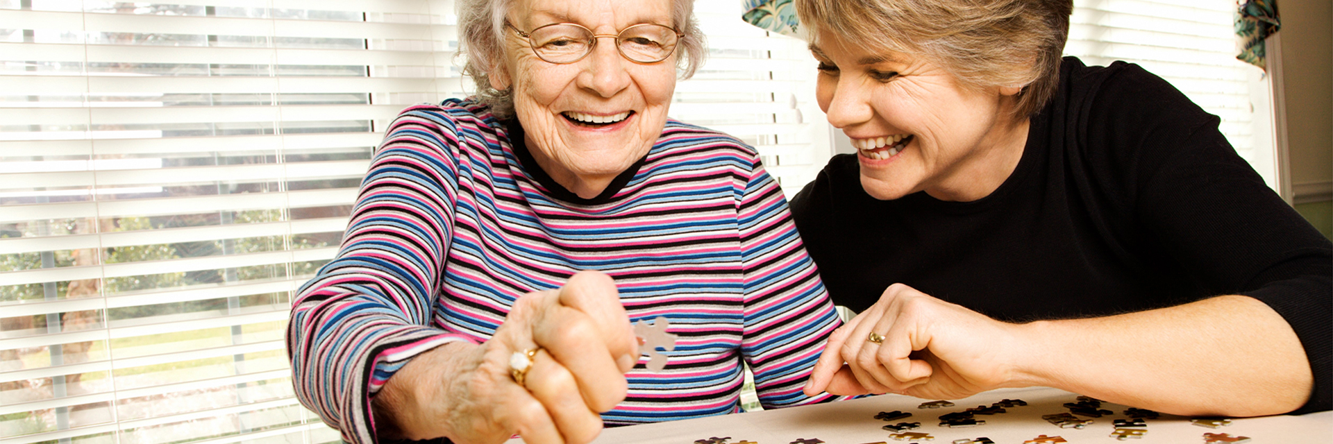 elderly playing puzzle with adult daughter